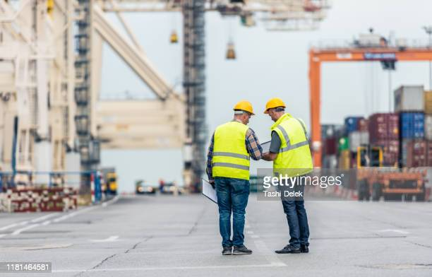 taking stock of the shipyard - longshoremen stock pictures, royalty-free photos & images
