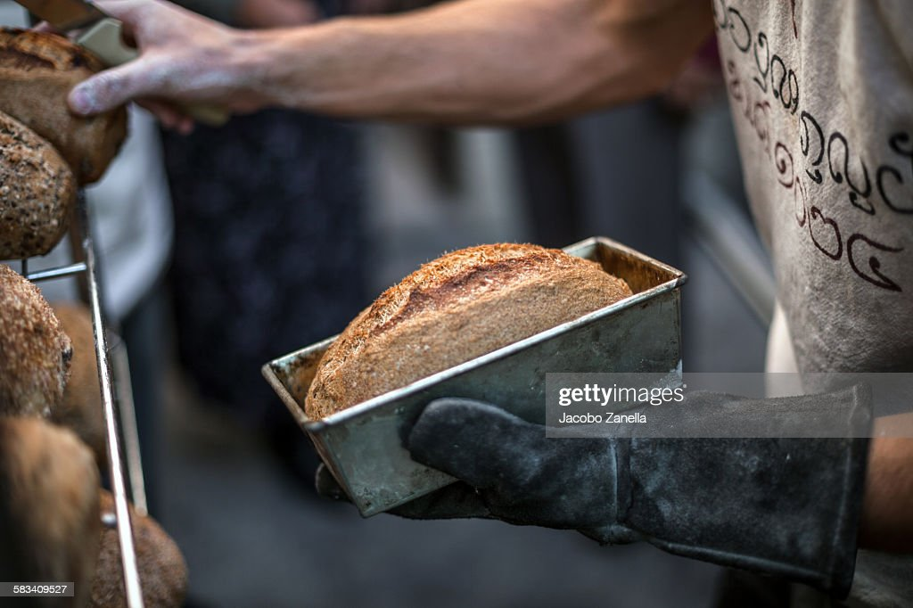 Taking the bread out of the loaf tin : Stock Photo