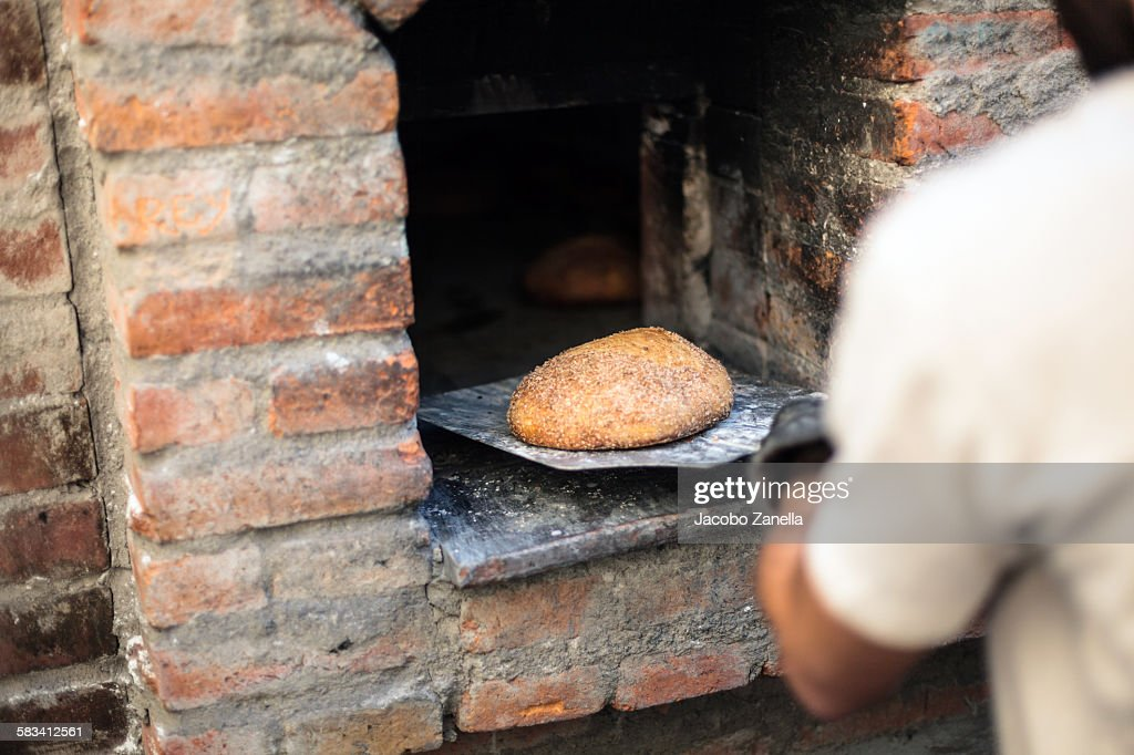 Taking the bread out of the oven : Stock Photo