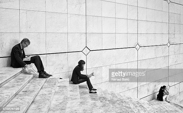CONTENT] Taking the lunch break on the steps of Grande Arche building at La Defense business district in Paris