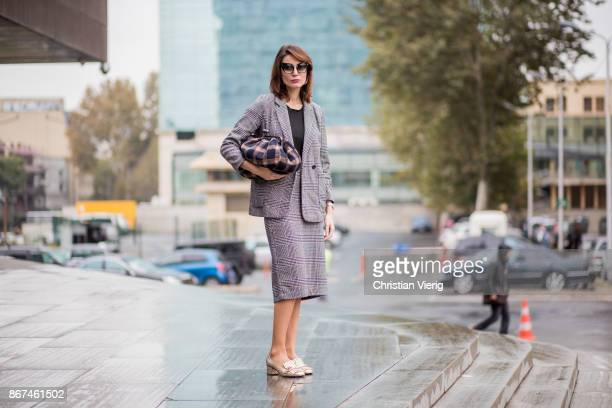 Tako Chkheidze wearing grey checked jacket checked skirt Gucci slippers checked clutch is seen during Tbilisi Fashion Week Spring/Summer 2018 on...