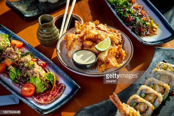 tako octopus tempura on restaurant table amid other japanese cuisine delicacies - takoyaki stock pictures, royalty-free photos & images