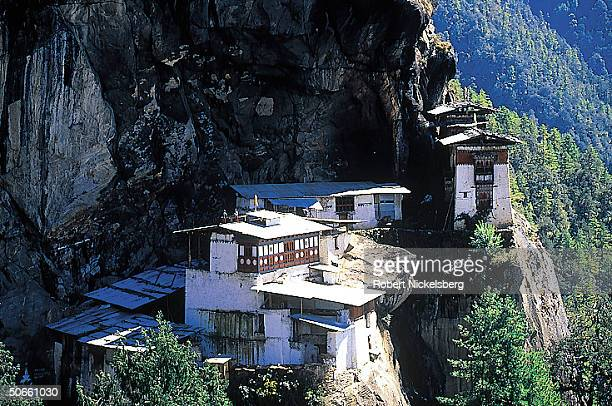Taktsang monastery at Tiger's Lair sacred Buddhist cave shrine perched high on cliff face of granite mountain