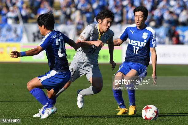 Taku Ushinohama of Tochigi SC controls the ball under pressure of Masanobu Matsufuji and Kazuki Ota of Azul Claro Numazu during the JLeague J3 match...