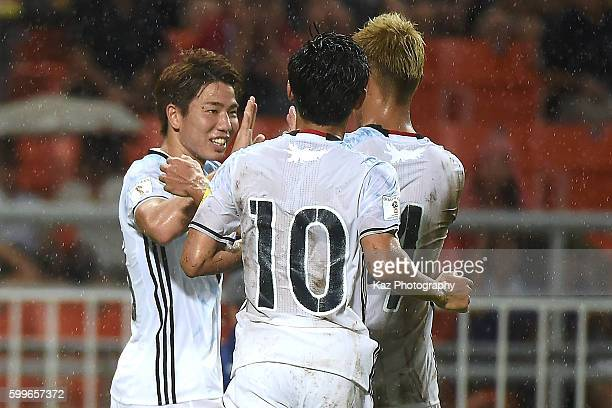 Takuma Asano celebrates with Shinji Kagawa and Keisuke Honda of Japan after scoring the second goal during the 2018 FIFA World Cup Qualifier between...