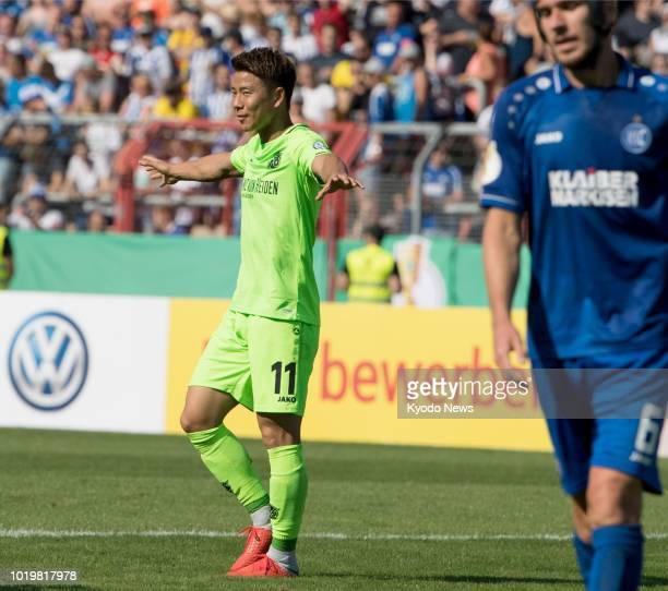 Takuma Asano celebrates after scoring on his debut for Hannover during the second half of the club's 60 win over thirddivision Karlsruher in the...