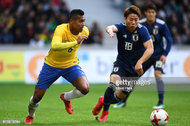Takuma Asano of Japan and Alex Sandro of Brazil compete for the ball during the international friendly match between Brazil and Japan at Stade...