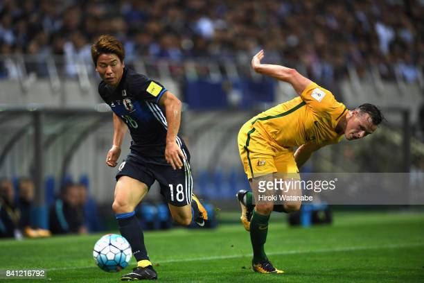 Takuma Asano of Japan and Brad Smith of Australia compete for the ball during the FIFA World Cup Qualifier match between Japan and Australia at...