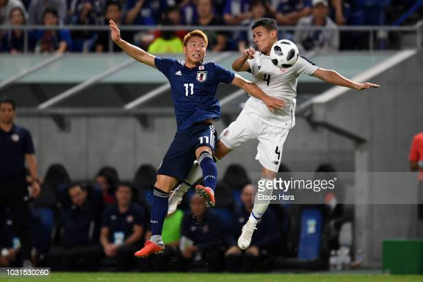Takuma Asano of Japan and Ian Smith of Costa Rica compete for the ball during the international friendly match between Japan and Costa Rica at Suita...