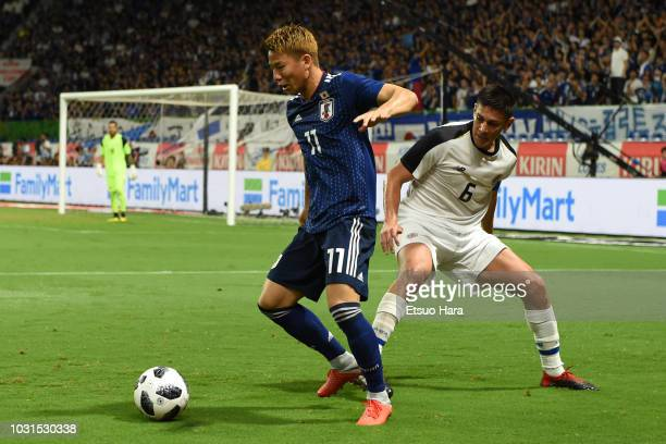 Takuma Asano of Japan and Oscar Duarte of Costa Rica compete for the ball during the international friendly match between Japan and Costa Rica at...