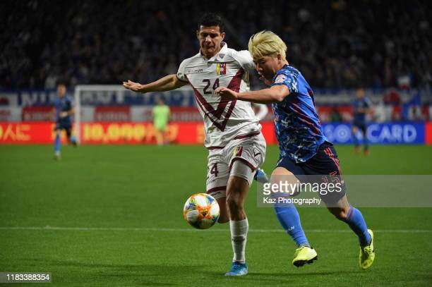 Takuma Asano of Japan and Yordan Osorio of Venezuela compete for the ball during the international friendly match between Japan and Venezuela at the...