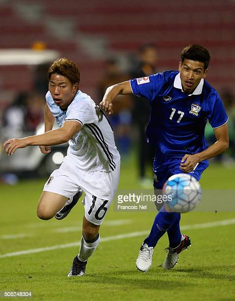 Takuma Asano of Japan battles for the ball with Tanaboon Keserat of Thailand during the AFC U23 Championship Group B match between Thailand and Japan...