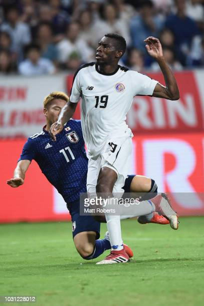Takuma Asano of Japan is tackled by Keyner Brown of Costa Rica during the international friendly match between Japan and Costa Rica at Suita City...