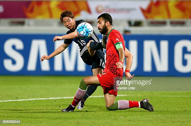 Takuma Asano of Japan is tackled by Roozbeh Cheshmi of Iran during the AFC U23 Championship quarter final match between Japan and Iran at the...