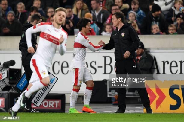 Takuma Asano of Stuttgart shakes hands with head coach Hannes Wolf after being substituted during the Second Bundesliga match between VfB Stuttgart...