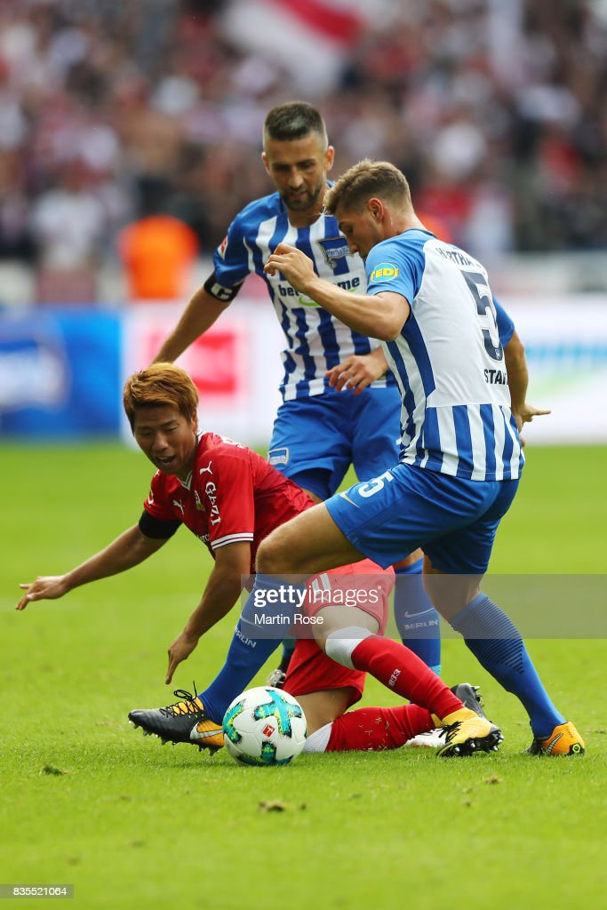 Takuma Asano of VfB Stuttgart (red) and Niklas Stark of Hertha BSC Berlin (5) and Vedad Ibisevic of Hertha BSC Berlin (back) during the Bundesliga match between Hertha BSC and VfB Stuttgart at Olympiastadion on August 19, 2017 in Berlin, Germany.