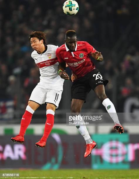 Takuma Asano of VfB Stuttgart is challenged by Salif Sane of Hannover 96 during the Bundesliga match between Hannover 96 and VfB Stuttgart at...