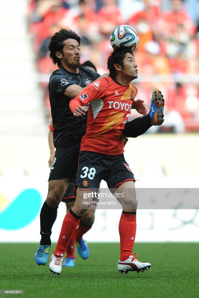 Takuma Edamura of Nagoya Grampus keeps the ball under pressure from Yuki Abe of Urawa Red Diamonds during the J. League match between Nagoya Grampus and Urawa Red Diamonds at the Toyota Stadium on April 12, 2014 in Toyota, Japan.