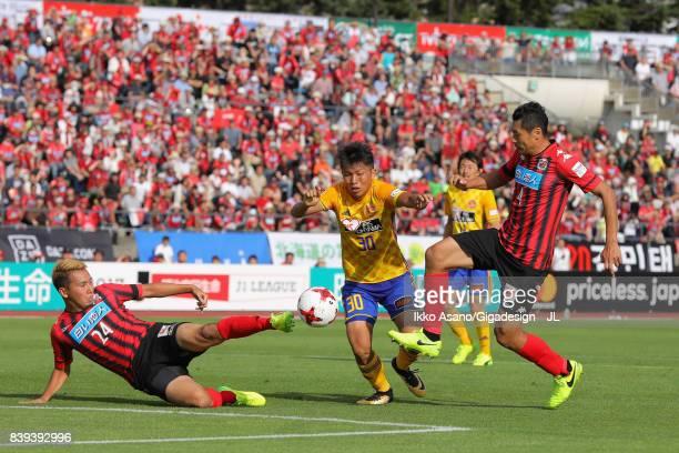 Takuma Nishimura of Vegalta Sendai controls the ball under pressure of Akito Fukumori and Ryuji Kawai of Consadole Sapporo during the JLeague J1...