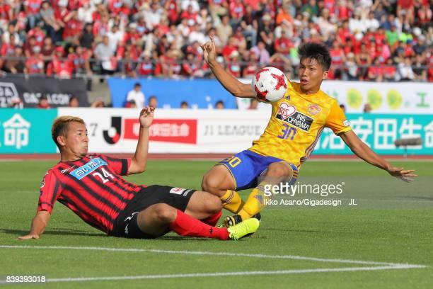 Takuma Nishimura of Vegalta Sendai is tackled by Akito Fukumori of Consadole Sapporo during the JLeague J1 match between Consadole Sapporo and...