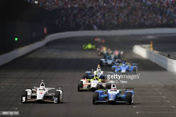 Takuma Sato of Japan driver of the Andretti Autosport Honda and Helio Castroneves of Brazil driver of the Shell Fuel Rewards Team Penske Chevrolet...