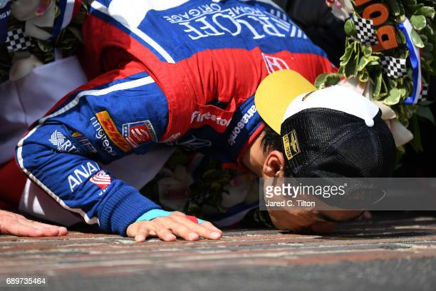 Takuma Sato of Japan, driver of the Andretti Autosport Honda, celebrates by kissing the bricks after winning the 101st Indianapolis 500 at...