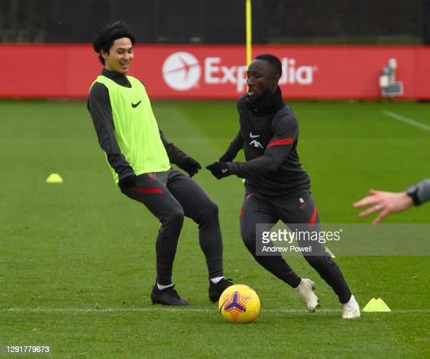 Takumi Minamino and Naby Keita of Liverpool during a training session at AXA Training Centre on December 17, 2020 in Kirkby, England.