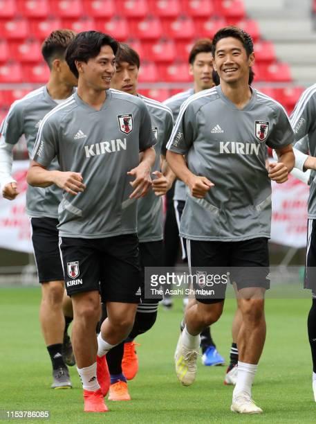 Takumi Minamino and Shinji Kagawa of Japan warm up during a training session ahead of the international friendly match between Japan and Trinidad...