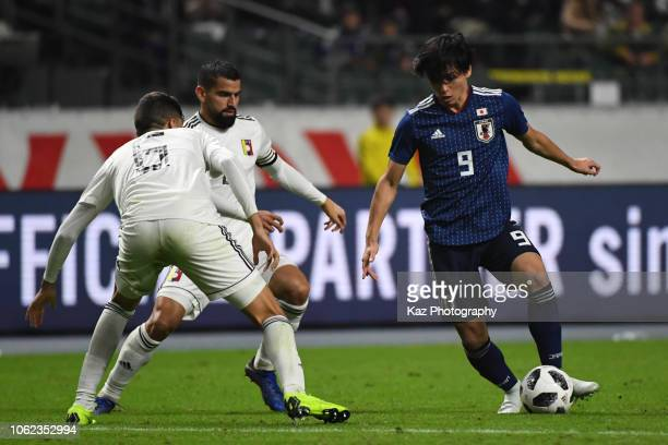Takumi Minamino dribbles the ball under the pressure from Tomas Rincon and Nahuel Ferraresi of Venezuela during the international friendly match...