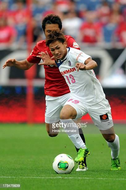 Takumi Minamino of Cerezo Osaka and Daisuke Nasu of Urawa Red Diamonds compete for the ball during the JLeague match between Urawa Red Diamonds and...
