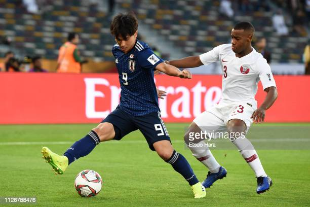 Takumi Minamino of Japan and Assim Omer Madibo of Qatar compete for the ball during the AFC Asian Cup final match between Japan and Qatar at Zayed...