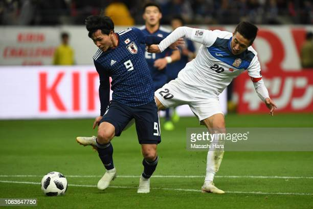 Takumi Minamino of Japan and Baktyiar Duishobekov of Kyrgyz compete for the ball during the international friendly match between Japan and Kyrgyz at...