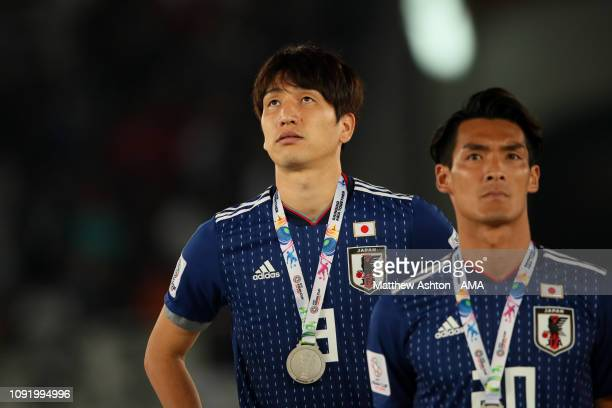 Takumi Minamino of Japan and his teammates look dejected at the end of the AFC Asian Cup final match between Japan and Qatar at Zayed Sports City...
