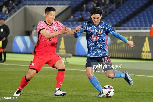Takumi Minamino of Japan and Kim Taehwan of South Korea compete for the ball during the international friendly match between Japan and South Korea at...