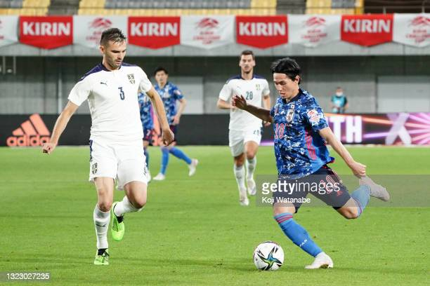 Takumi Minamino of Japan and Marko Petkovic of Serbia compete for the ball during the international friendly match between Japan and Serbia at Noevir...