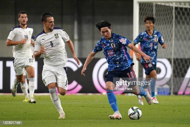 Takumi Minamino of Japan and Nemanja Maksimovic of Serbia compete for the ball during the international friendly match between Japan and Serbia at...