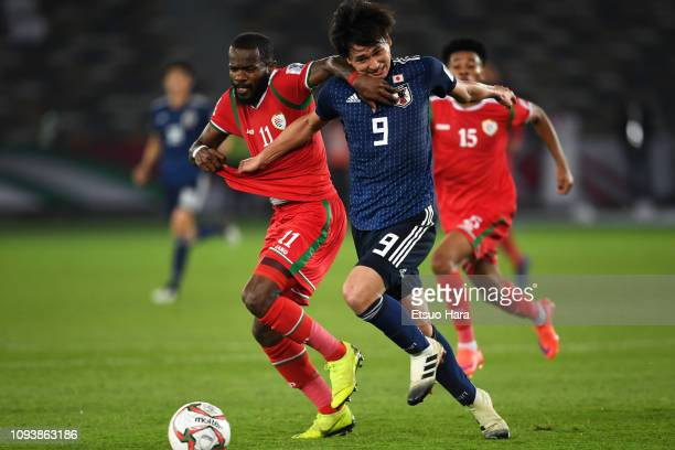 Takumi Minamino of Japan and Saad Al Mukhaini of Oman compete for the ball during the AFC Asian Cup Group F match between Oman and Japan at Zayed...