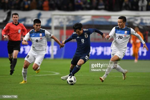 Takumi Minamino of Japan Baktyiar Duishobekov and Aziz Sydykov of Kyrgyz compete for the ball during the international friendly match between Japan...