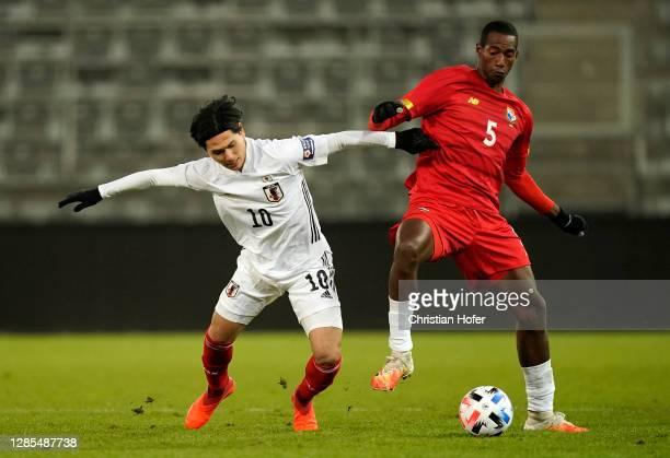 Takumi Minamino of Japan battles for possession with Abdiel Ayarza of Panama during the international friendly match between Japan and Panama at...