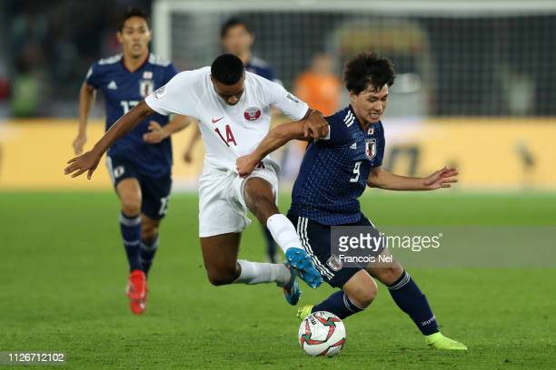 Takumi Minamino of Japan battles for possession with Salem Al Hajri of Qatar during the AFC Asian Cup final match between Japan and Qatar at Zayed...