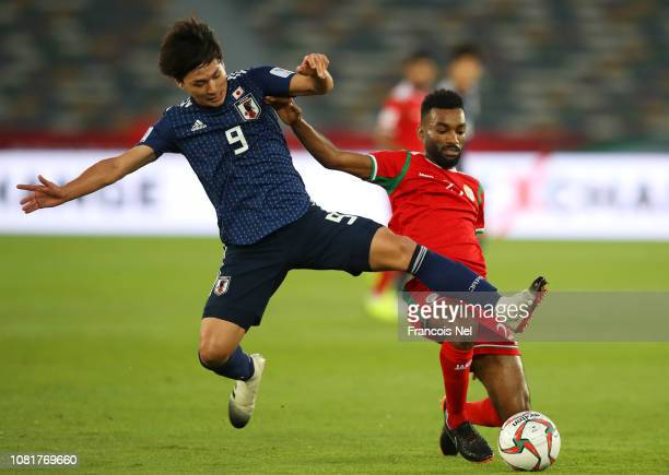 Takumi Minamino of Japan battles for the ball with Harib AlSaadi of Oman during the AFC Asian Cup Group F match between Oman and Japan at Zayed...