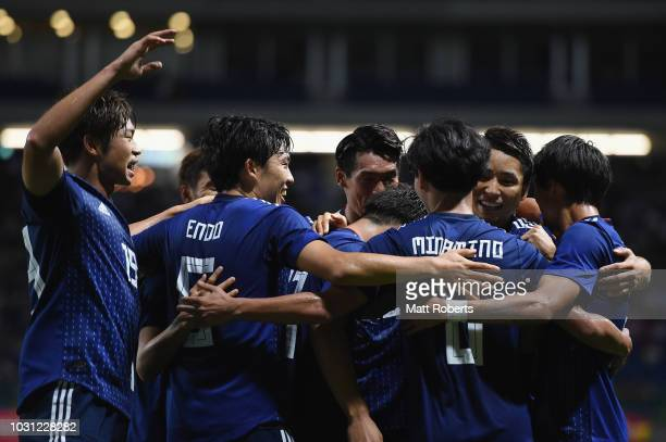 Takumi Minamino of Japan celebrates scoring a goal with team mates during the international friendly match between Japan and Costa Rica at Suita City...