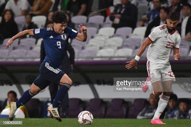 Takumi Minamino of Japan dribbles the ball under the pressure from Rezaeiansemeskandi Ramin of Iran during the AFC Asian Cup semi final match between...