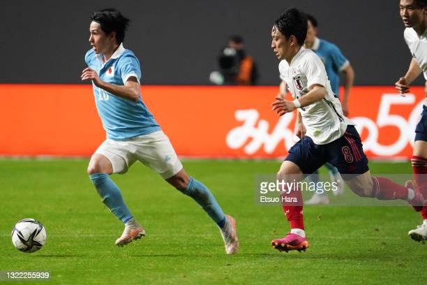Takumi Minamino of Japan goes past Koji Miyoshi of Japan U-24 during the friendly match between Japan and Japan U-24 at the Sapporo Dome on June 03,...