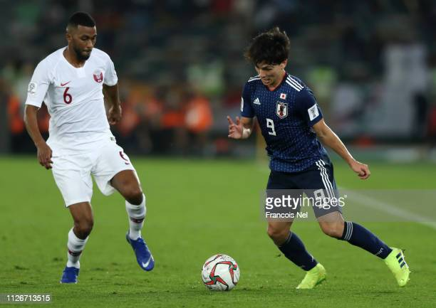 Takumi Minamino of Japan in action while under pressure from Abdelaziz Hatim of Qatar during the AFC Asian Cup final match between Japan and Qatar at...