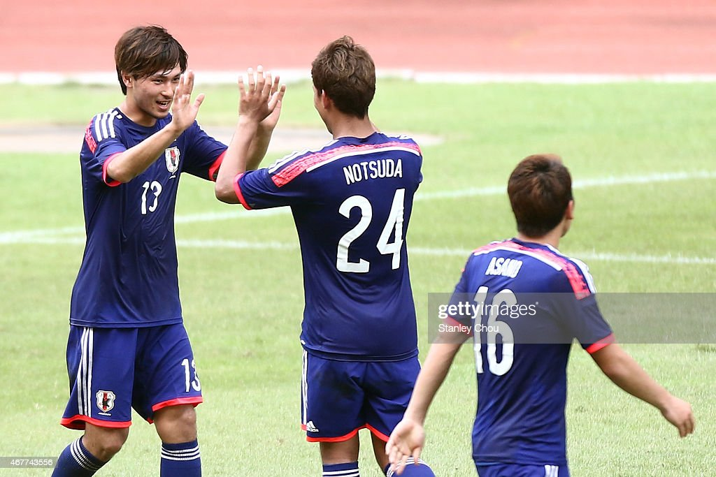 Takumi Minamino #13 of Japan is congratulated by Gakuto Notsuda after scoring his team's seventh goal against Macau during the AFC U23 Championship Qualifier Group I match between Japan and Macau at Shah Alam Stadium on March 27, 2015 in Shah Alam, Malaysia.