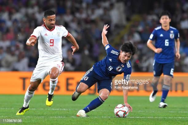 Takumi Minamino of Japan is tackled by Zarandini Omid Ebrahimi of Iran during the AFC Asian Cup semi final match between Iran and Japan at Hazza Bin...