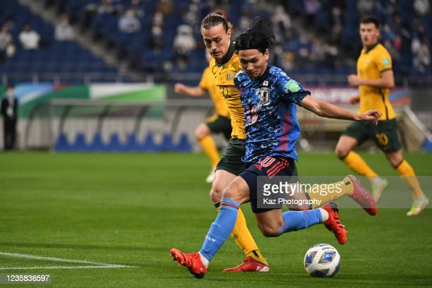 Takumi Minamino of Japan keeps the ball under the pressure from Jackson Irvine of Australia during the FIFA World Cup Asian qualifier final round...