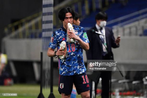 Takumi Minamino of Japan kisses his shoes after his side's 4-1 victory in the FIFA World Cup Asian Qualifier 2nd round Group F match between Japan...