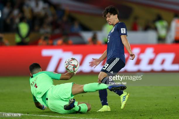 Takumi Minamino of Japan scores his team's first goal past Saad Al Sheeb of Qatar during the AFC Asian Cup final match between Japan and Qatar at...